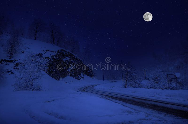Majestic winter night in a mountain valley with full moon in a starry sky. Beautifulsnowy night landscape with moon stock image