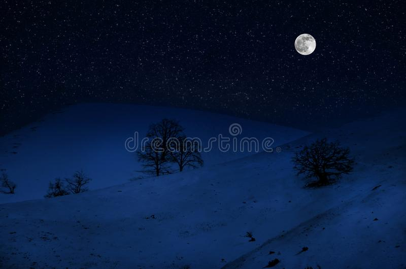 Majestic winter night in a mountain valley with full moon in a starry sky. Beautifulsnowy night landscape with moon stock photo