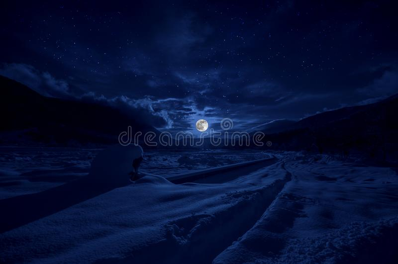 Majestic winter night in a mountain valley with full moon in a starry sky. Beautifulsnowy night landscape with moon stock photography