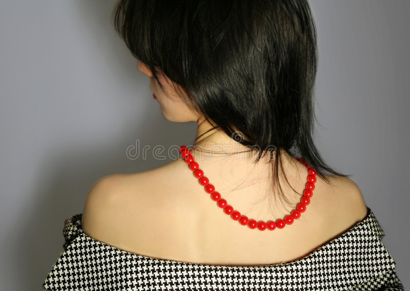 Majestic woman. Young woman with red beads on her back looks aside royalty free stock photography