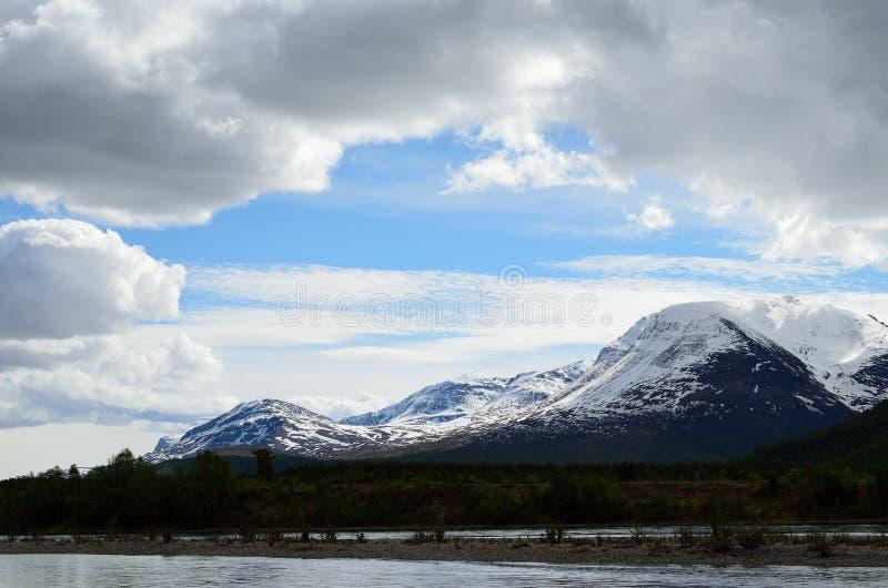 Majestueus sneeuwberg en rivierlandschap in de vroege zomer stock afbeeldingen