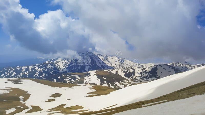 Majestueuze die Bergpieken met Sneeuw en stijgende blauwe hemel worden behandeld royalty-vrije stock afbeelding