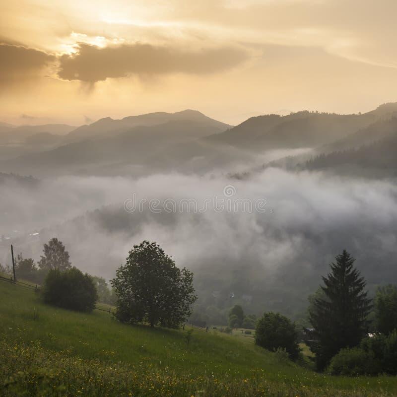 Majestueuze mening over mooie mistbergen in mistlandschap Dramatische ongebruikelijke scène De achtergrond van de reis Het onderz royalty-vrije stock fotografie