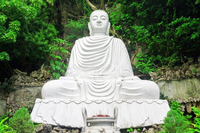 Majestueuze mening van het witte standbeeld van Boedha onder gebladerte van bomen royalty-vrije stock fotografie