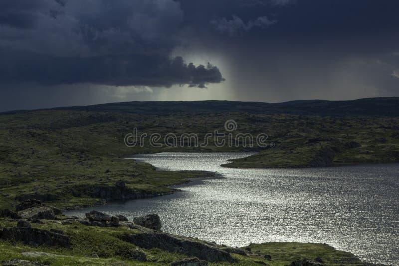 Majestueuze stormachtige hemel en zonstralen over een meer in de bergen stock foto