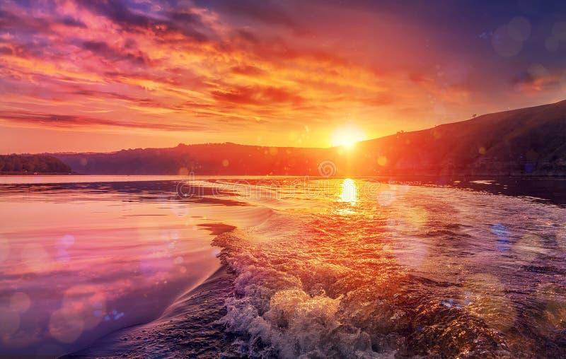 Majestueuze zonsondergang op de rivier Kleurrijke wolken over de golven van de motorboot stock fotografie