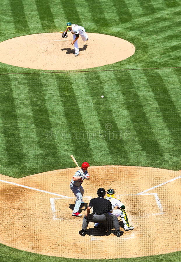 Major League Baseball Pitcher vs Batter. A pitcher for the Oakland Athletics delivers a pitch towards a St. Louis Cardinlas batter at home plate during a Major royalty free stock images