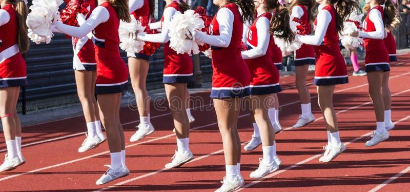 Majorettes de lycée encourageant pendant la partie de football photo libre de droits