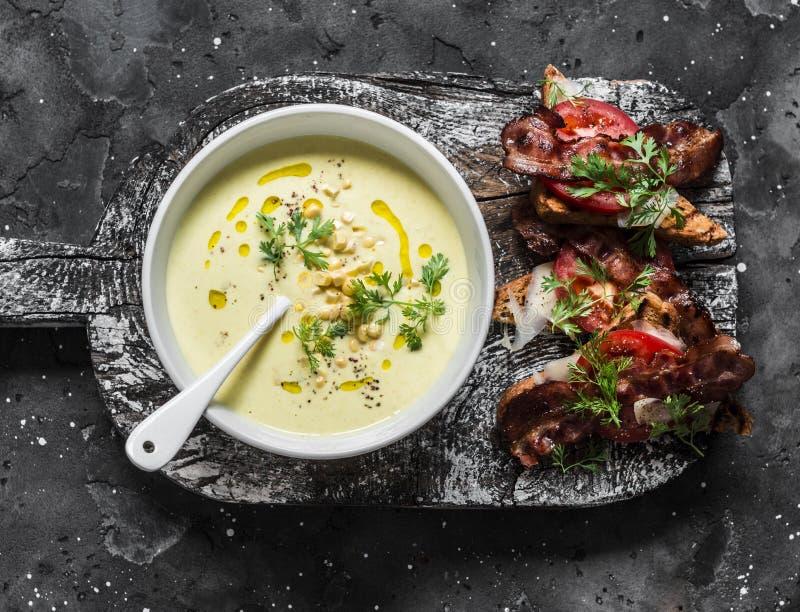Majs mosade soppa med rostat bröd för bröd för korn för bacontomatparmesan helt på mörk bakgrund, bästa sikt arkivfoto
