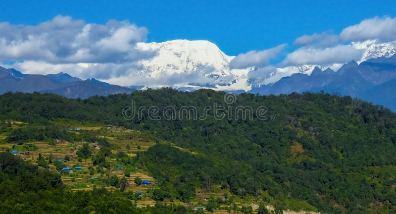 Makalu mountain landscape, rice fields and forests in the foreground, Nepal. Panoramic view of Makalu mountain in the background, rice fields and forests in the stock photos