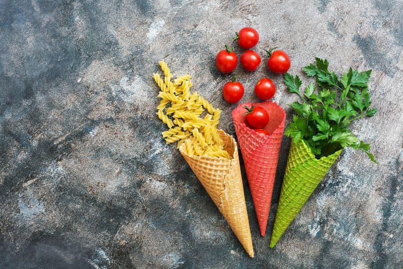 Makaron, czereśniowy pomidor i pietruszka w barwionym opłatku, konusujemy na nieociosanym abstrakcjonistycznym tle Widok od above fotografia royalty free