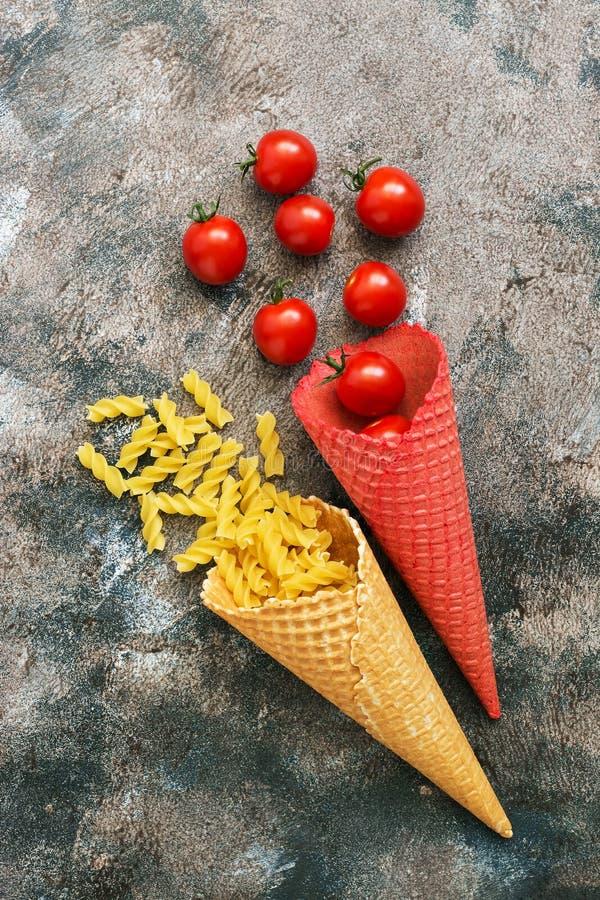 Makaron i pomidory w barwiącym gofrze konusujemy na nieociosanym tle Odgórny widok, koszt stały, mieszkanie nieatutowy zdjęcia royalty free
