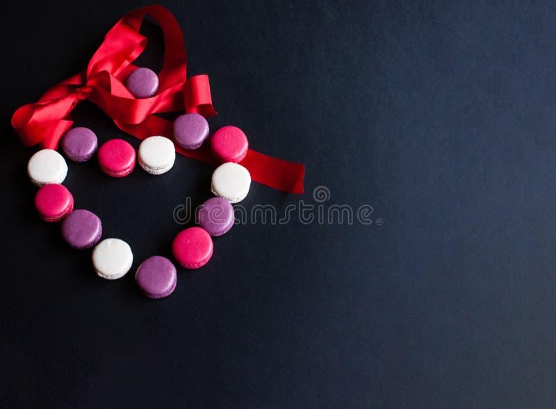 Makaron op een zwarte achtergrond in de vorm van een hart met rood lint wordt opgemaakt dat Kleurrijke amandelkoekjes, pastelkleu stock fotografie