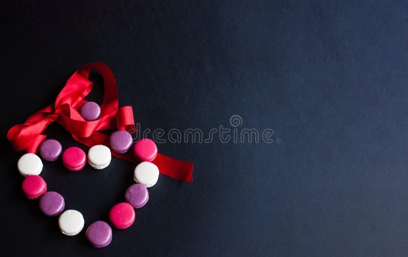 Makaron op een zwarte achtergrond in de vorm van een hart met rood lint wordt opgemaakt dat Kleurrijke amandelkoekjes, pastelkleu royalty-vrije stock afbeelding