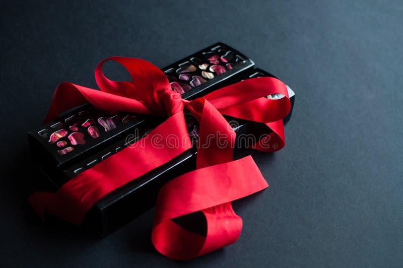 Makaron op zwarte achtergrond met rood lint, kleurrijke amandelkoekjes, pastelkleuren stock foto