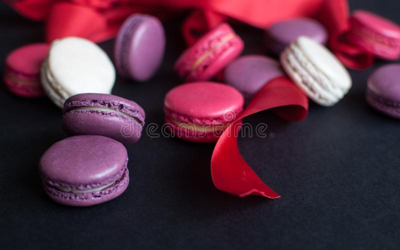 Makaron op zwarte achtergrond met rood lint, kleurrijke amandelkoekjes, pastelkleuren stock afbeelding