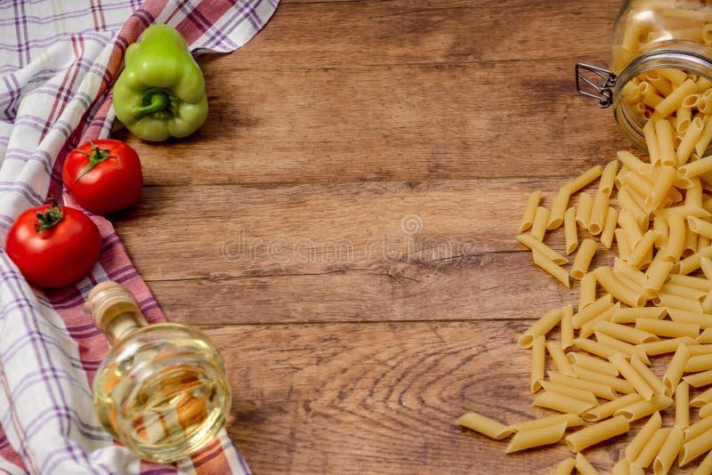 Makaron, pomidory, papryka i olej na drewniany stołowym przygotowywającym dla kulinarnego makaronu, obrazy royalty free