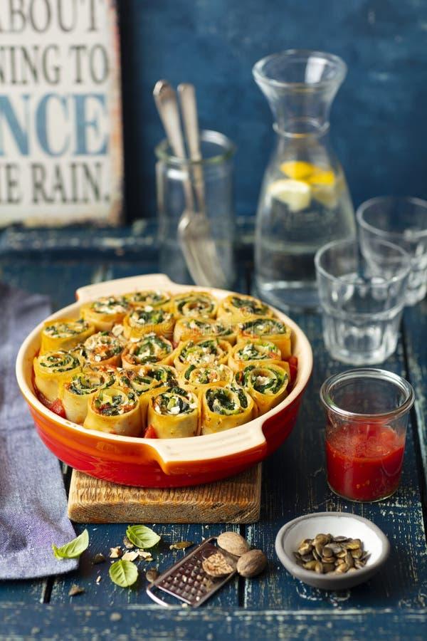 Makaron rolki robić z lasagne i wypełniać z szpinakami i feta, piec w pomidorowym kumberlandzie zdjęcia stock