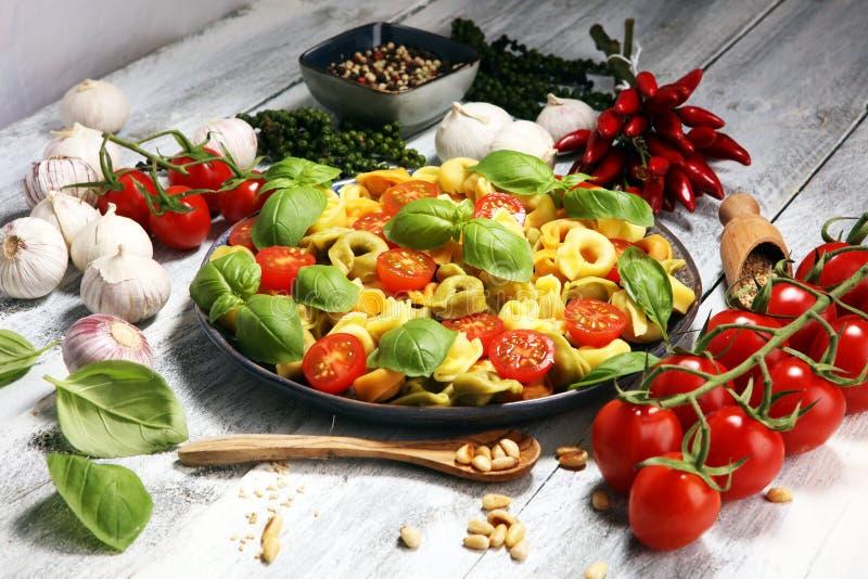 Makaron tricolor tortellini makaronu sałatka z pomidorami i cebule na drewnie zgłaszamy tło zdjęcia royalty free