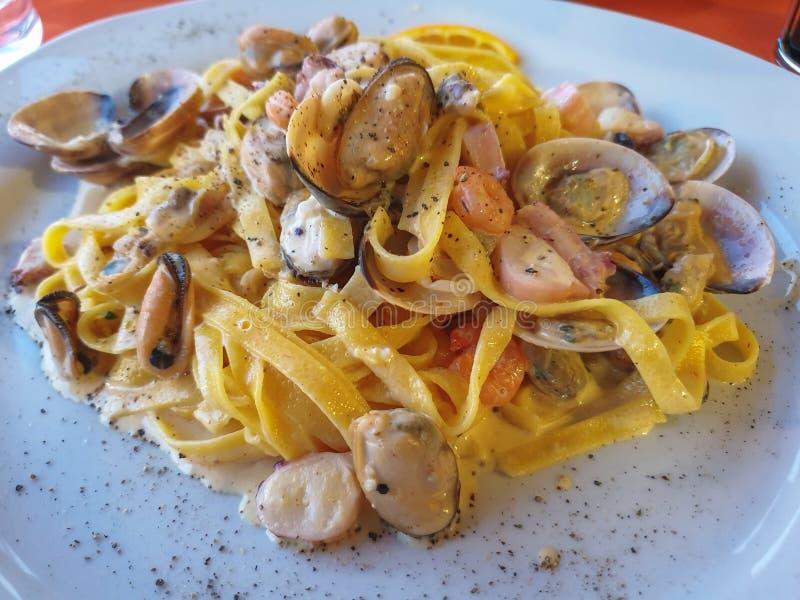 Makaron z denną owoc w bielu talerzu z miękkim światłem, kąta widok Spaghetti Ai Frutti Di Klacz, owoce morza śródziemnomorski ga zdjęcia royalty free
