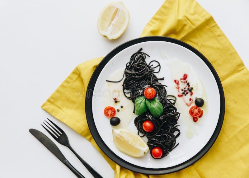 Makaron z kałamarnica atramentem i salat na bielu stole z żółtą pieluchą zdjęcie royalty free