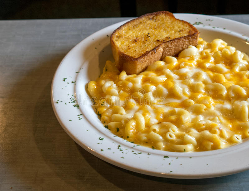 Makaroni och ost med vitlökbröd arkivfoto