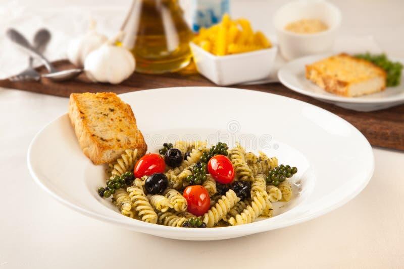 Makaronitrådar, ny peppar och svarta oliv Med vitlökbre royaltyfria bilder