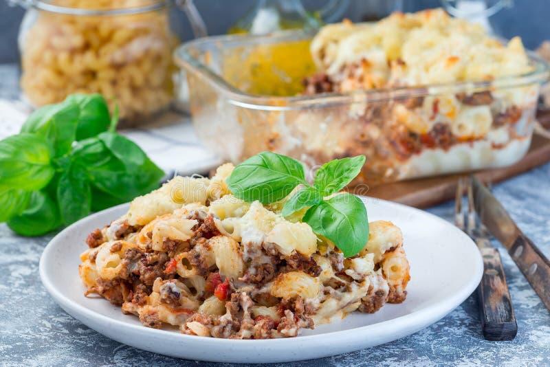 Makaronowa potrawka z zmieloną wołowiną, serem i pomidorem na talerzu, horyzontalnym fotografia royalty free