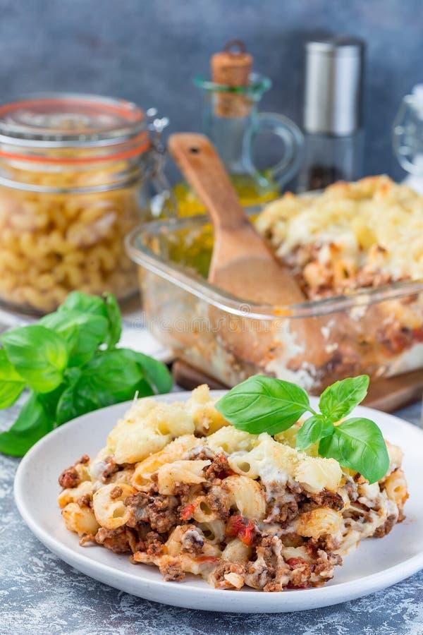 Makaronowa potrawka z zmieloną wołowiną, serem i pomidorem na talerzu, pionowo fotografia royalty free