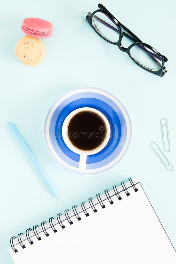 Makarons, een kop van zwarte koffie, een open nota met witte pagina, pen, glazen op een pastelkleur blauwe achtergrond Beeld voor stock afbeelding