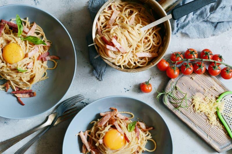 Makaronu carbonara z bekonem i parmesan w szarość talerzach na stole, restauracyjny serw alla aubergine tła kuchni świeżych włosk fotografia stock