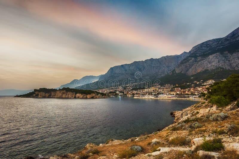 Makarska Kroatien Sikt av stranden och den gamla staden på solnedgången arkivbilder