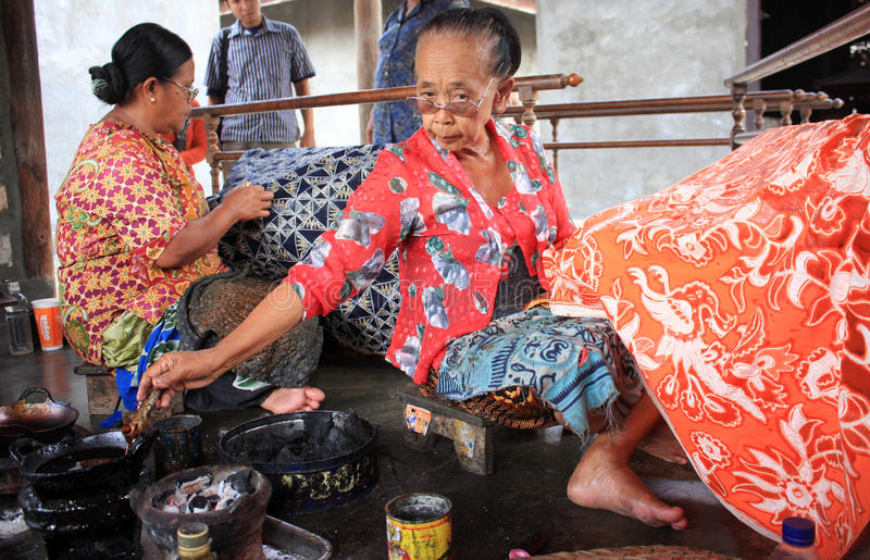 Make batik. Two old ladies make batik on cloth with canting in Solo royalty free stock photo