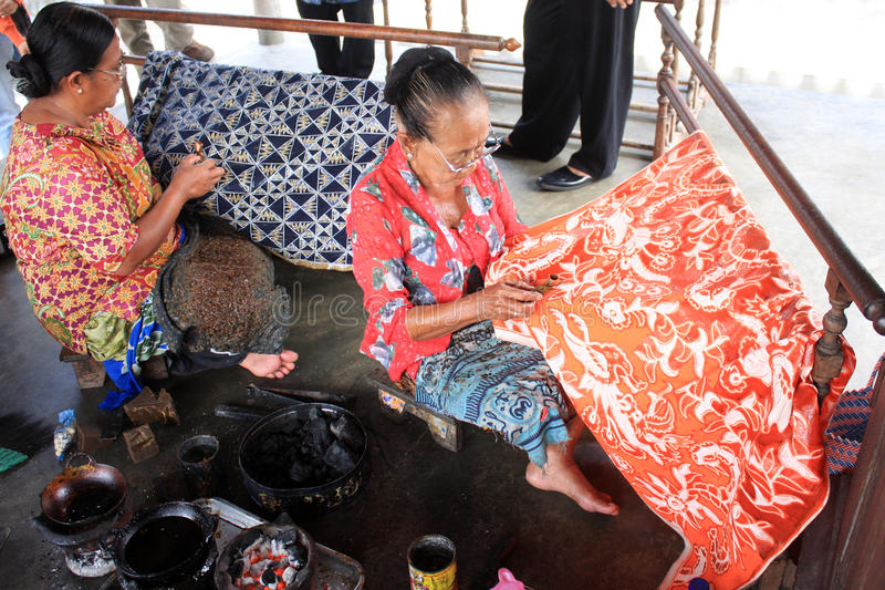 Make batik. Two old ladies make batik on cloth with canting in Solo stock photo