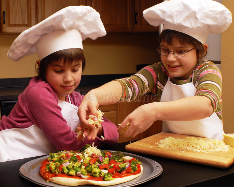 Make it Cheezie!. Sisters in aprons and chef's hats spreading cheese on the pizza they're making