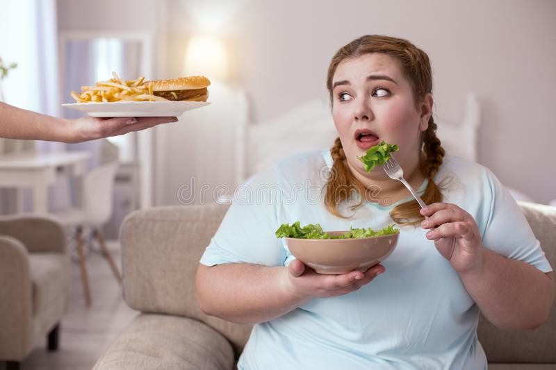 Stout red-head woman deciding which type of food to choose. Make a choice. Chubby young woman sitting on the sofa while making choice between healthy and junk stock photo