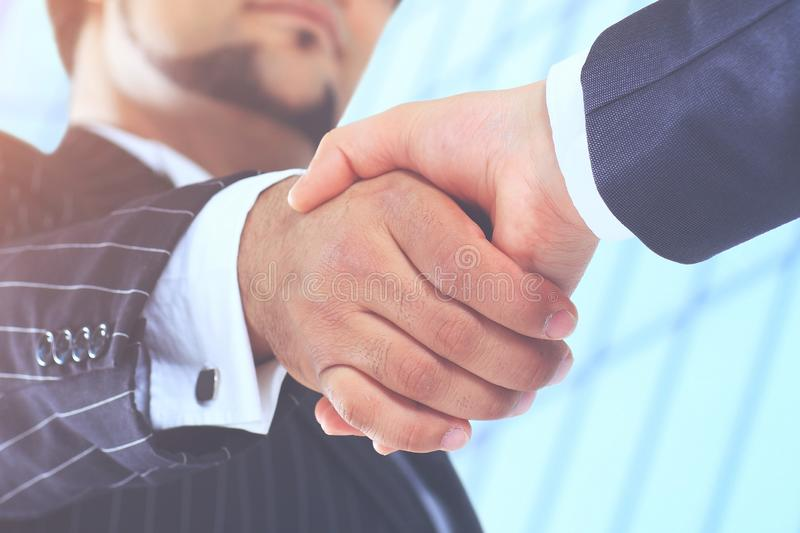 Make a deal. Handshake shot from low angle against the background of the business center. Make a deal. Handshake shot from a low angle against a background of royalty free stock photo