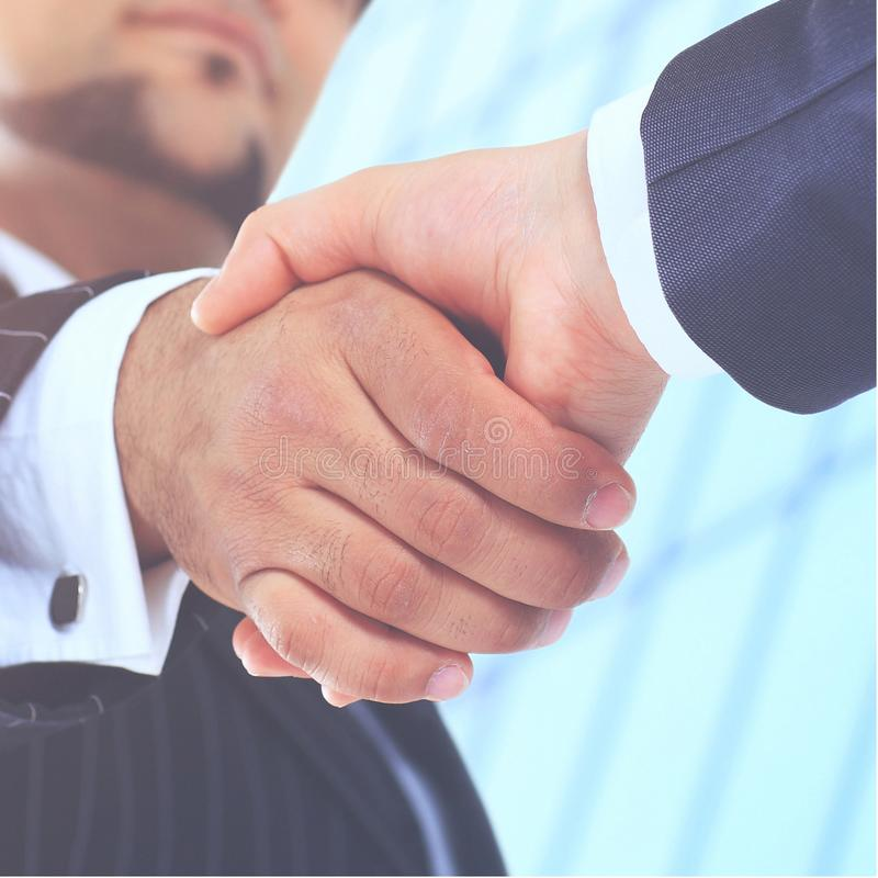 Make a deal. Handshake shot from  low angle against the background of the business center. Make a deal. Handshake shot from a low angle against a background of stock photo