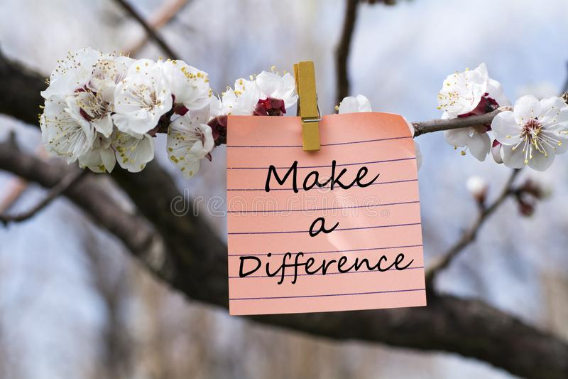 Make a difference in memo. Pined on tree with blooms stock photo