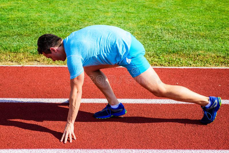Make effort for victory. Man athlete runner stand low start position stadium path. Runner ready to go. Adult runner. Prepare race at stadium. How to start stock photography