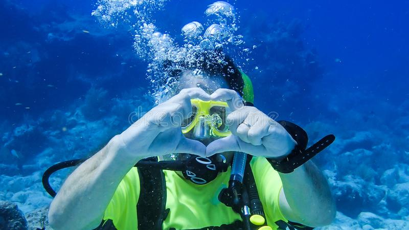 Make för dykapparatdykning som berättar hans fru att han älskar hennes undervattens- royaltyfri foto