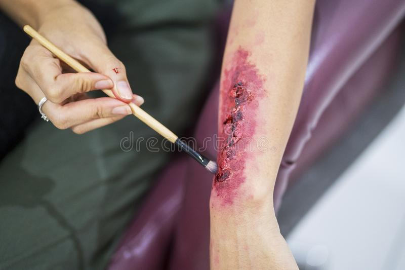 Make a fake bloody wound on hand with makeup royalty free stock photography