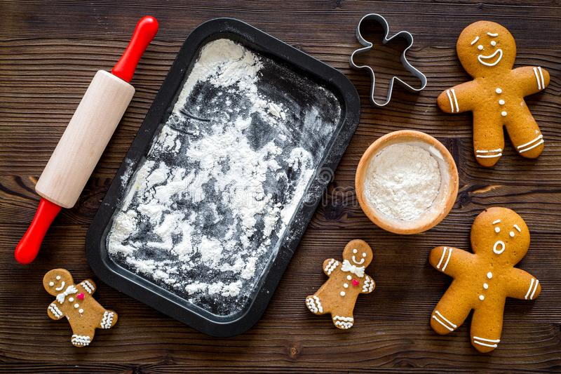 Make gingerbread cookie for new year 2018. Gingerbread man, rolling pin, flour on dark wooden background top view mockup royalty free stock photos
