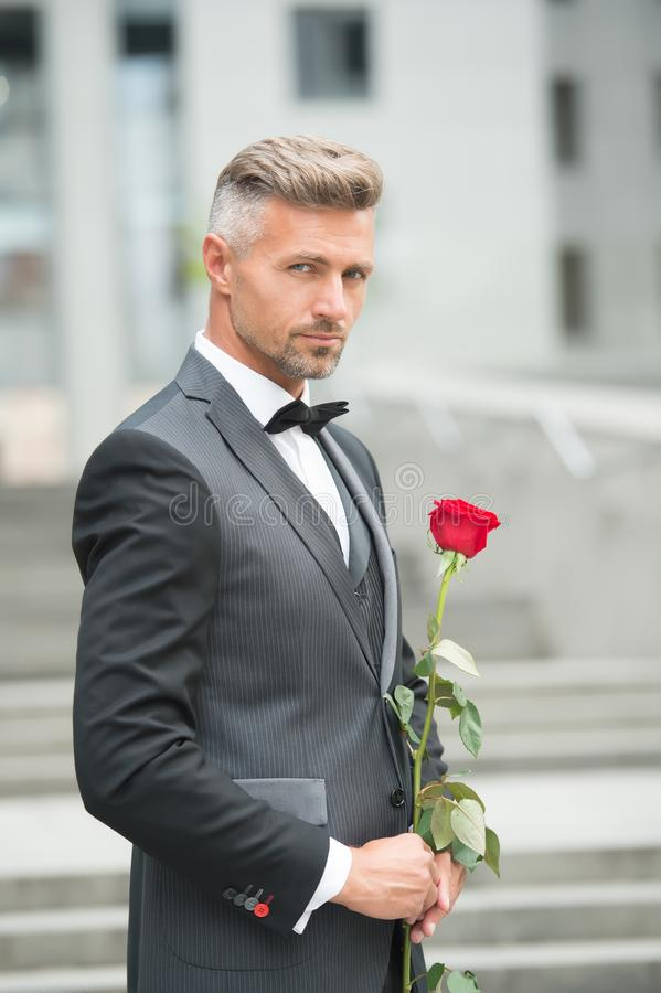 Make good first impression. Valentines day and anniversary. Handsome guy rose flower romantic date. Well groomed macho royalty free stock photos