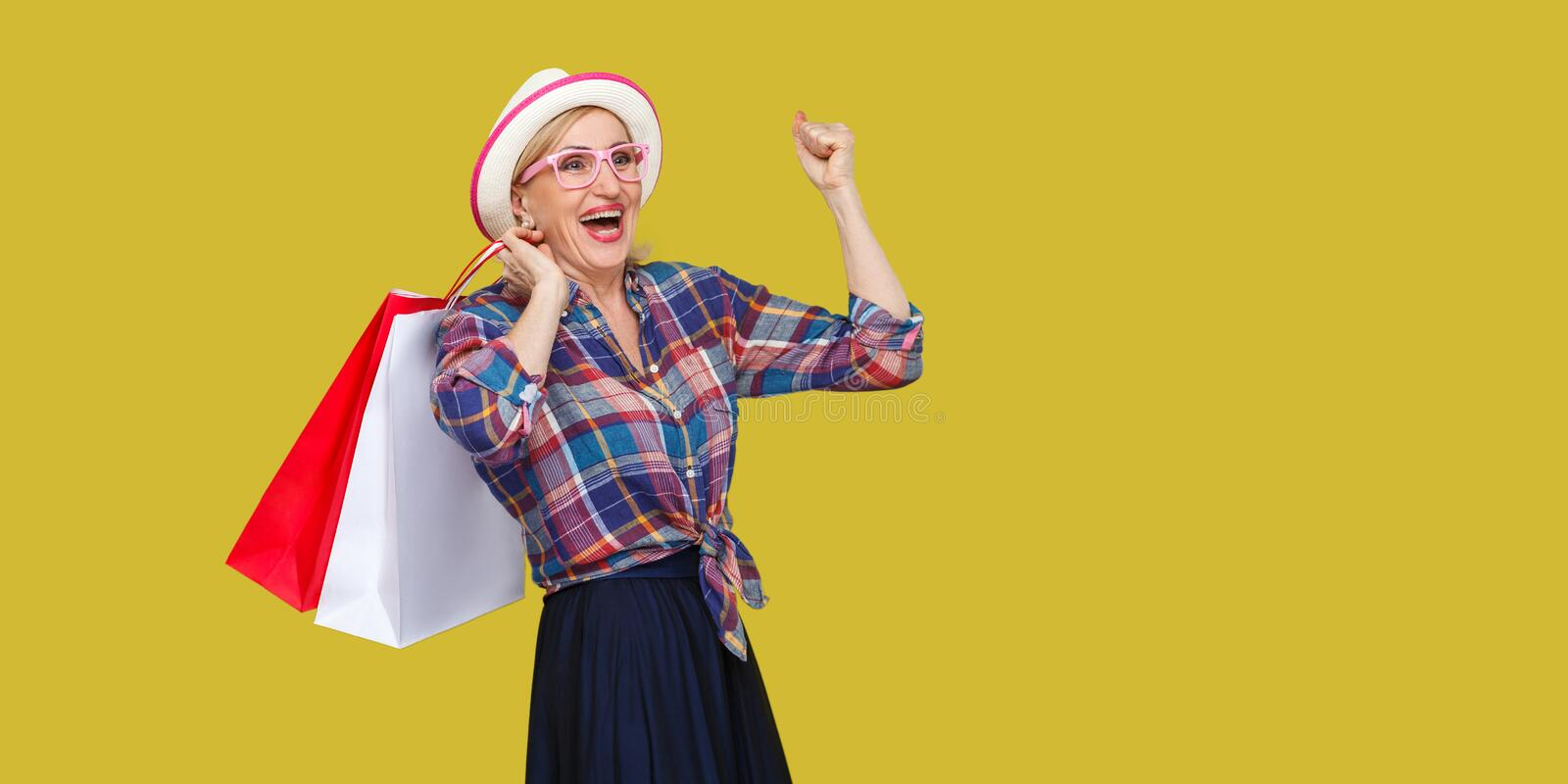 Make a great shopping! Satisfied modern granny in white hat and in checkered shirt holding shopping bags and triumphing with royalty free stock photo