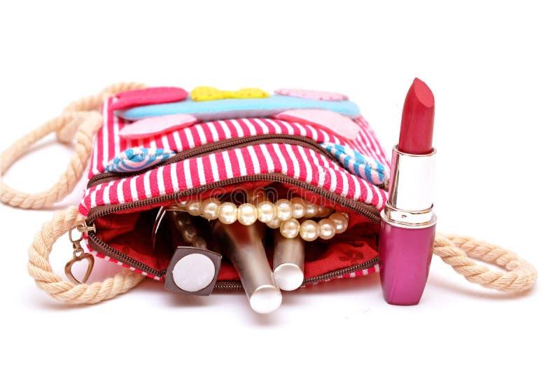 Make kit lipstick nail polish coming out of girl handy bag.  stock photo