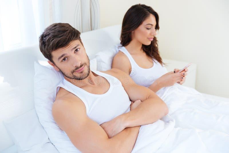 Make, medan hans internetknarkarefru använder mobiltelefonen royaltyfri bild