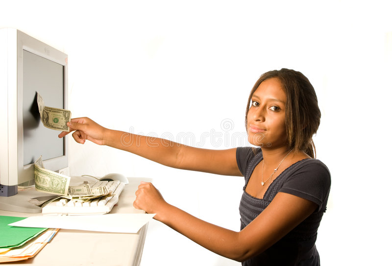 Make money from the Internet. A teenage Hispanic girl pulling dollar bills from the computer. Making money from the internet and the computer. Can also be useful stock photography