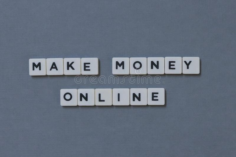 ' Make Money Online ' word made of square letter word on grey background royalty free stock image