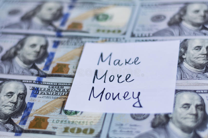 Make more money note on a dollar bills background royalty free stock photography
